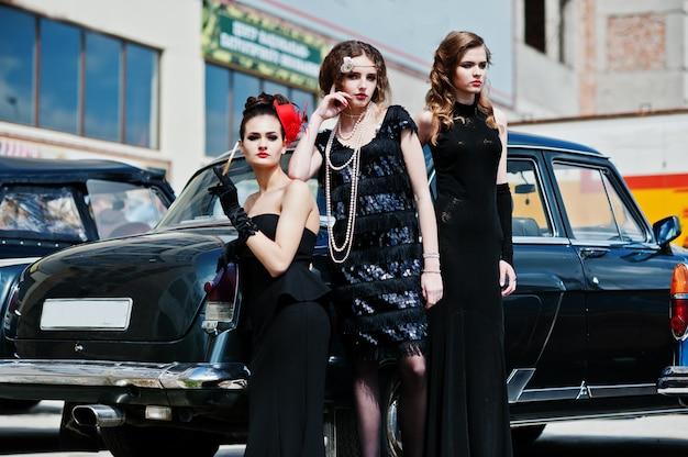 Jong meisje drie in retro stijlkleding dichtbij oude klassieke uitstekende auto's.