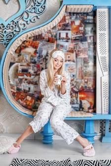 Jong meisje drinkt koffie in pyjama's en slippers. slaapmasker