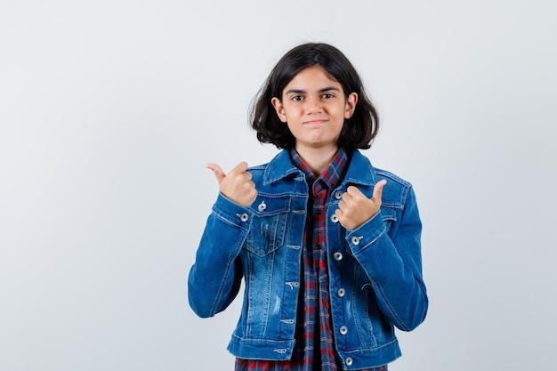 Jong meisje duimen opdagen met beide handen in geruit hemd en spijkerjasje en op zoek gelukkig, vooraanzicht.