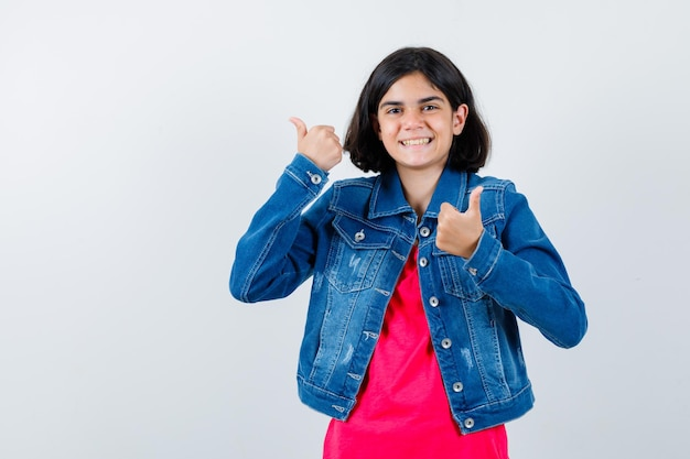 Jong meisje duimen opdagen met beide handen in rood t-shirt en jean jas en er gelukkig uitzien. vooraanzicht.