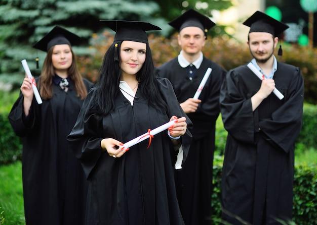 Jong meisje, een universitair afgestudeerde student in een zwart gewaad en een vierkante hoed met een diploma in haar handen, glimlacht tegen de achtergrond van de klasgenoten van de studenten.