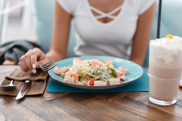 Jong meisje eet in een restaurant. caesarsalade met kip en melkcocktail op tafel. women's handen