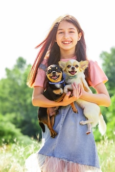 Jong meisje en honden buiten. twee chihuahua-honden in wapens. wandelen met huisdieren.