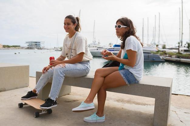 Jong meisje en skater model vriend zittend op een bankje in de haven