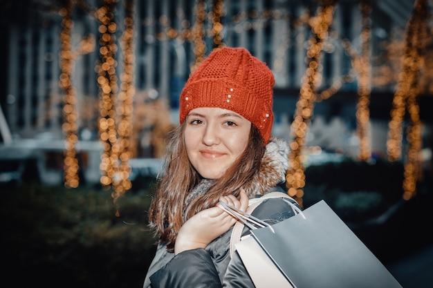 Jong meisje gaat bedrijf boodschappentassen wandelen in de buurt van in de stad