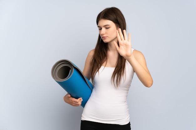 Jong meisje gaat naar yogalessen terwijl ze een mat vasthoudt die stopgebaar maakt en teleurgesteld
