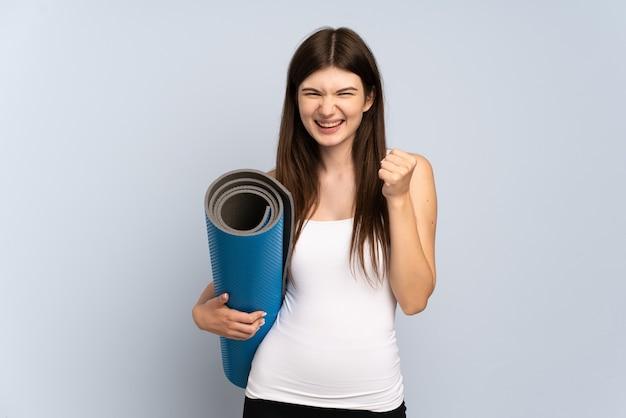 Jong meisje gaat naar yogalessen terwijl ze een mat vasthoudt en een overwinning in de winnaarspositie viert