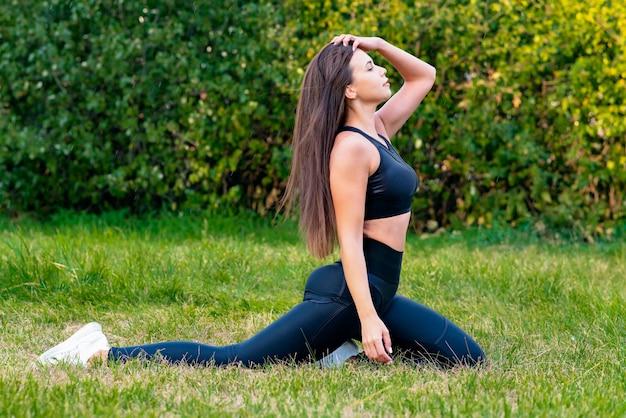 Jong meisje gaat sporten in de parkvrouw die zich uitstrekt in fitness
