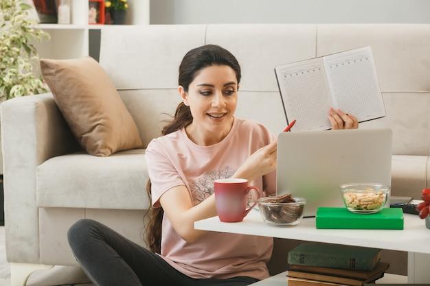 Jong meisje gebruikte laptop vasthouden en punten met pen op notebook zittend op de vloer achter de salontafel in de woonkamer