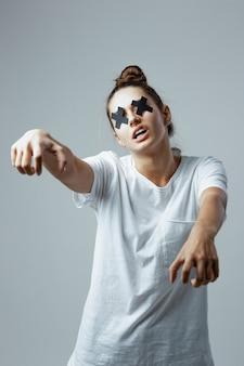Jong meisje gekleed in wit t-shirt en spijkerbroek met zwarte kruisen van plakband op de ogen staat op de witte achtergrond in de studio als een zombie.