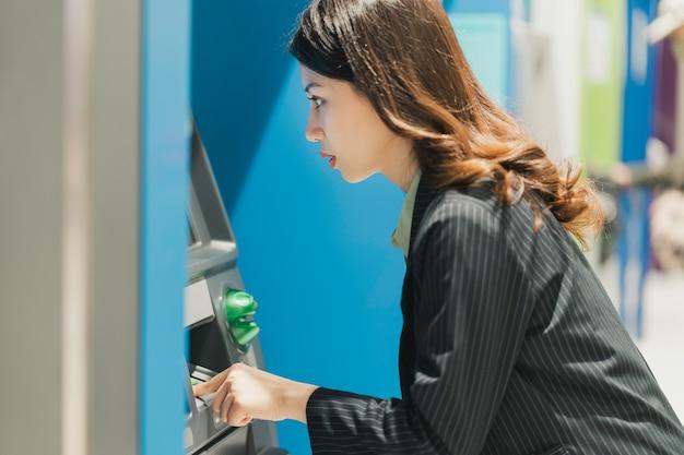 Jong meisje geld opnemen in het winkelcentrum