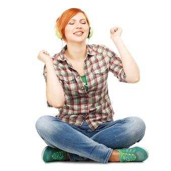 Jong meisje genieten van het luisteren naar muziek op koptelefoon geïsoleerd op wit