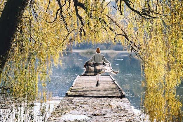 Jong meisje genieten van schoonheid herfst in de natuur vrouw met geruite sjaal wandelen in herfst seizoen