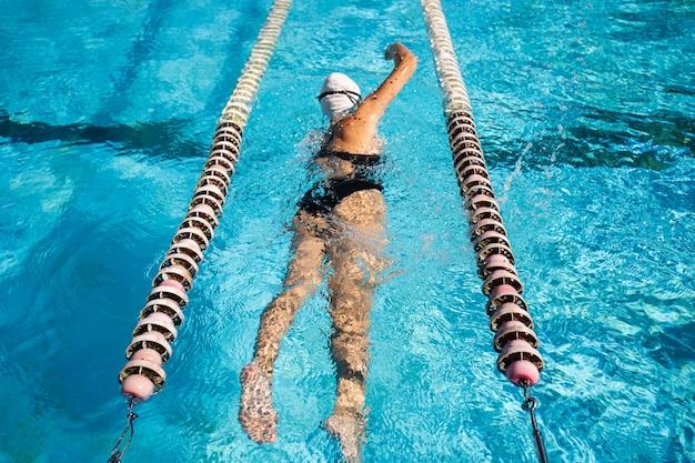 Jong meisje genieten van zwemmen bij het zwembad