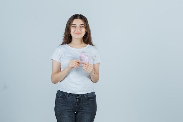 Jong meisje geschenkdoos houden terwijl kijken naar doos in t-shirt, spijkerbroek en op zoek vrolijk, vooraanzicht.