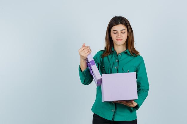 Jong meisje geschenkdoos openen in groene blouse, zwarte broek en gericht kijken. vooraanzicht.