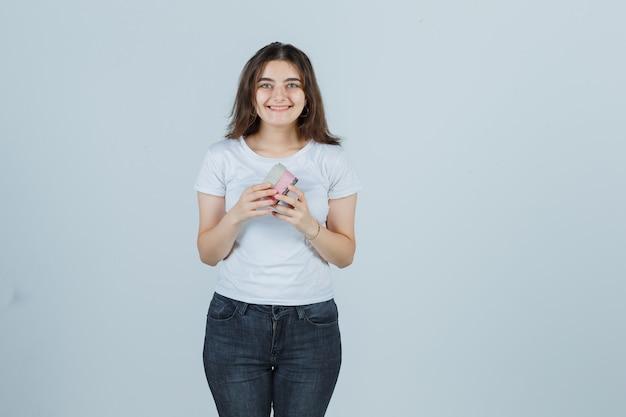 Jong meisje geschenkdoos openen tijdens het kijken naar camera in t-shirt, spijkerbroek en op zoek gelukkig, vooraanzicht.