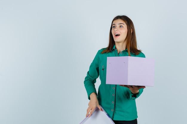 Jong meisje geschenkdoos openen, wegkijken in groene blouse, zwarte broek en verbaasd, vooraanzicht kijken.