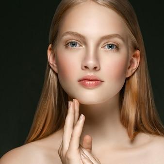Jong meisje gezicht schoonheid huid portret met lang blond haar met hand over donkere achtergrond. studio opname.
