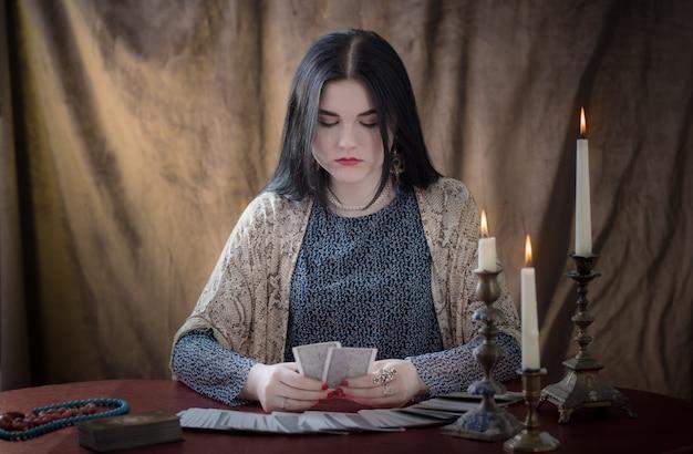 Jong meisje gissen met tarotkaarten op bruine achtergrond