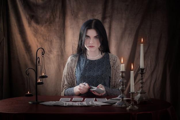 Jong meisje gissen met tarotkaarten op bruine ondergrond