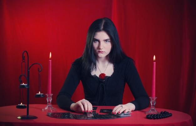 Jong meisje gissen met tarotkaarten op rode achtergrond