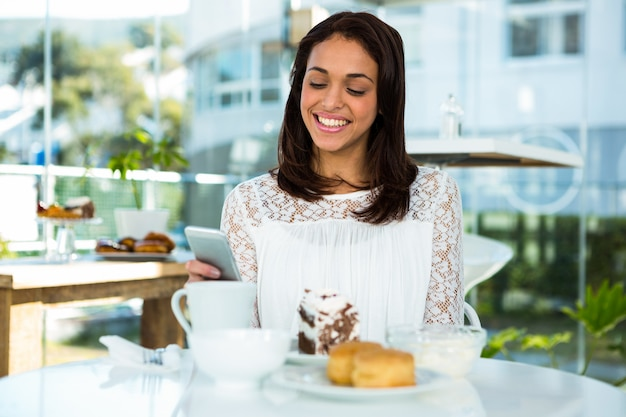 Jong meisje glimlachend maakt gebruik van haar telefoon door het nemen van thee