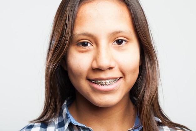 Jong meisje glimlachend met apparatuur op haar tanden