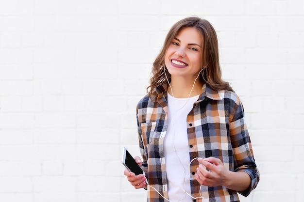 Jong meisje glimlacht en luistert naar muziek op de telefoon