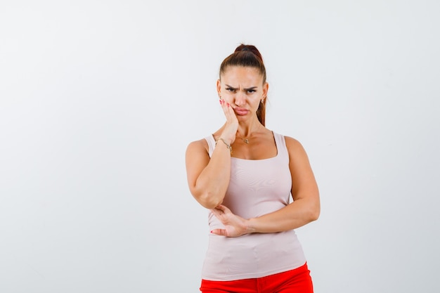 Jong meisje hand in de buurt van de mond, grimassen terwijl poseren in beige top en rode broek en op zoek ernstig, vooraanzicht.