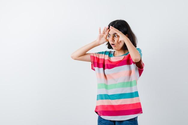 Jong meisje hand in hand in de buurt van gezicht in kleurrijk gestreept t-shirt en kijkt verrast, vooraanzicht.