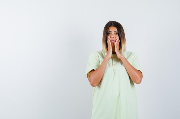 Jong meisje hand in hand in de buurt van mond in t-shirt en op zoek verrast. vooraanzicht.