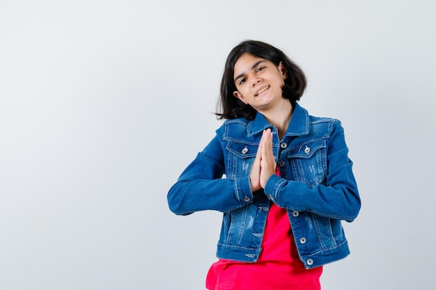 Jong meisje hand in hand in gebedspositie in rood t-shirt en spijkerjasje en ziet er vrolijk uit. vooraanzicht.