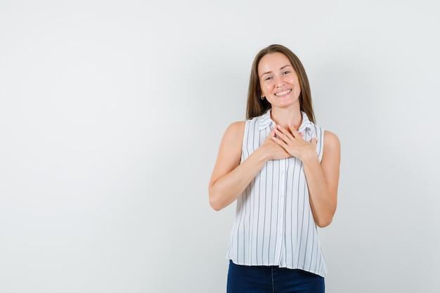 Jong meisje hand in hand op de borst in t-shirt, spijkerbroek en op zoek joviaal, vooraanzicht.