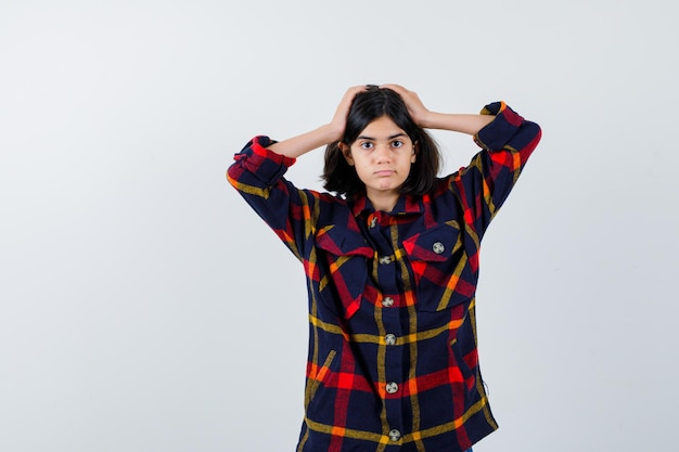 Jong meisje hand in hand op het hoofd in een geruit overhemd en ziet er serieus uit. vooraanzicht.