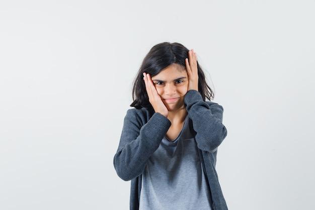 Jong meisje hand in hand op het hoofd in een lichtgrijs t-shirt en een donkergrijze hoodie met ritssluiting en kijkt geïrriteerd,