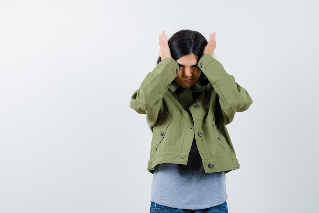 Jong meisje hand in hand op het hoofd in grijze trui, kaki jas, jeansbroek en kijkt geïrriteerd. vooraanzicht.