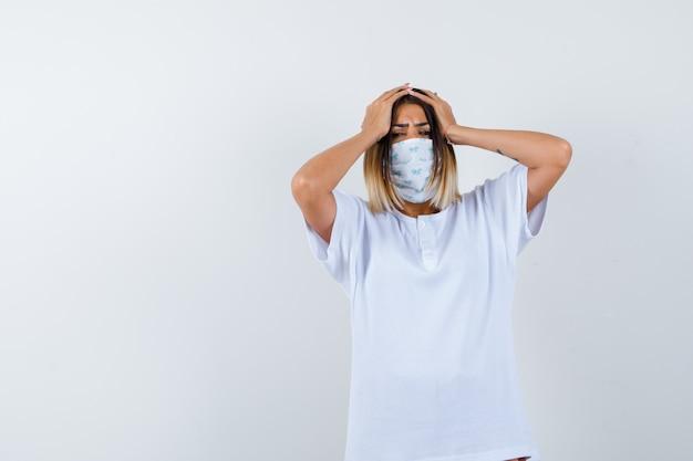 Jong meisje hand in hand op het hoofd in wit t-shirt en masker en op zoek bezorgd. vooraanzicht.