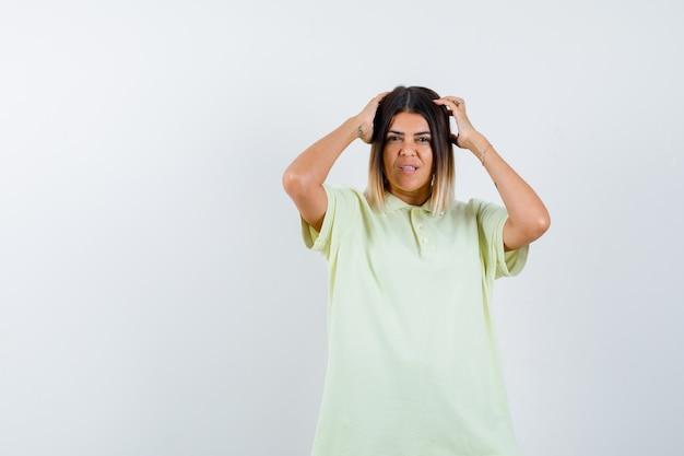 Jong meisje hand in hand op hoofd in t-shirt en op zoek ongemakkelijk, vooraanzicht.