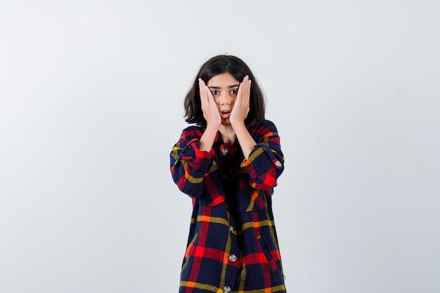 Jong meisje hand in hand op wangen in geruit overhemd en verbaasd kijken. vooraanzicht.