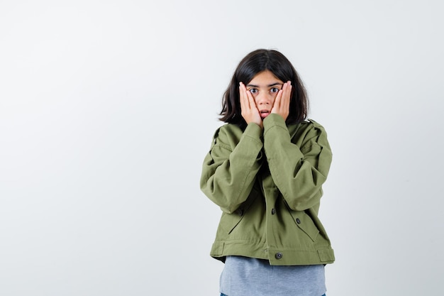 Jong meisje hand in hand op wangen in grijze trui, kaki jas, jeans broek en verbaasd kijken. vooraanzicht.