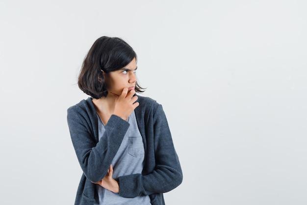 Jong meisje hand op de kin, iets nadenken terwijl ze wegkijkt in een lichtgrijs t-shirt en een donkergrijze hoodie met ritssluiting en peinzend kijkt