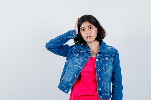 Jong meisje hand op het hoofd in rood t-shirt en jeans jasje en verbaasd kijken. vooraanzicht.