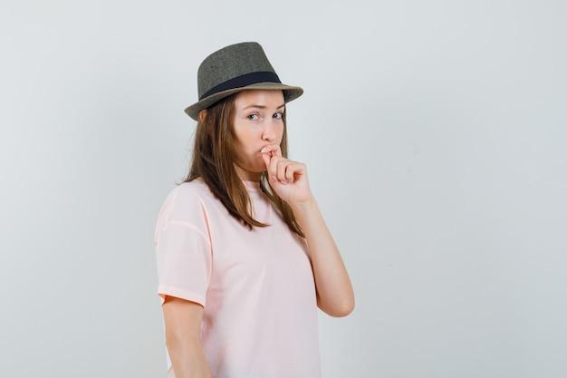 Jong meisje hand op kin in roze t-shirt, hoed en aarzelend op zoek. vooraanzicht.