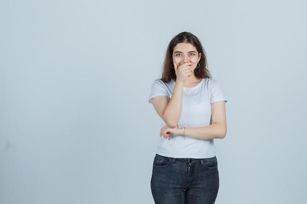 Jong meisje hand op kin in t-shirt, spijkerbroek en op zoek vrolijk. vooraanzicht.
