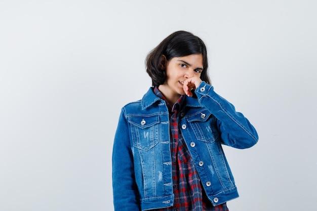 Jong meisje hand op mond, glimlachend in geruit overhemd en spijkerjasje en gelukkig kijken. vooraanzicht.