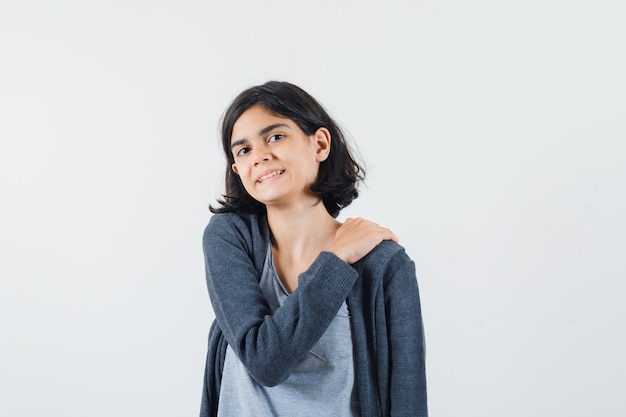 Jong meisje hand op schouder in lichtgrijs t-shirt en donkergrijze hoodie met ritssluiting en ziet er schattig uit,