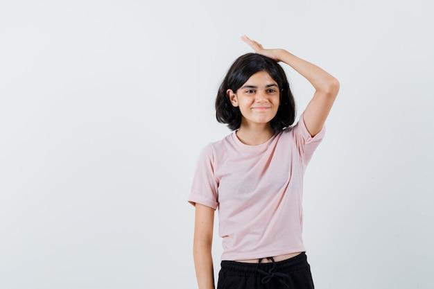 Jong meisje hand zetten hoofd in roze t-shirt en zwarte broek en schattig op zoek