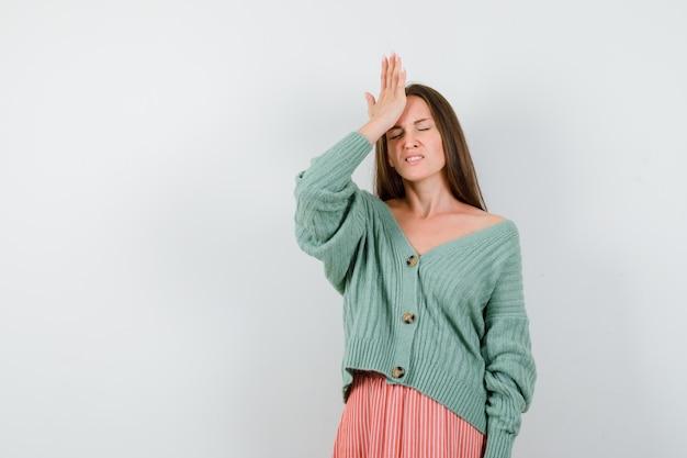 Jong meisje hand zetten voorhoofd, met hoofdpijn in breigoed, rok en uitgeput op zoek. vooraanzicht.