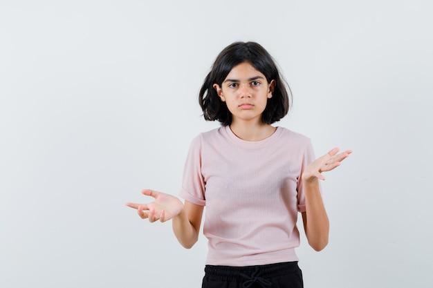 Jong meisje handen op vragende wijze in roze t-shirt en zwarte broek uitrekken en op zoek perplex